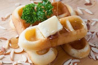 Close-up despejando mel do topo de waffles e porcas que tem salsa e queijo no topo dos waffles no prato de madeira para o café da manhã.