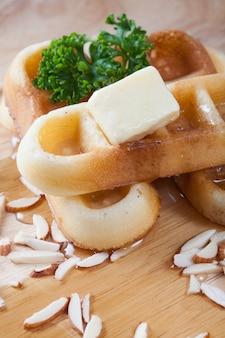 Close-up despeje o mel do topo dos waffles e porcas, que tem salsa e queijo no topo dos waffles no prato de madeira para o café da manhã.
