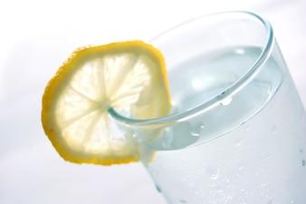 Close-up do copo de água com uma fatia de limão
