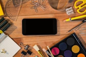 Close-up do telefone móvel com vários artigos de papelaria