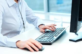 Close-up do trabalhador trabalhar com mouse e teclado