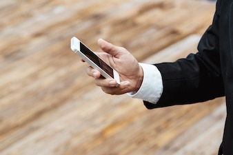 Close-up inteligente Homem de negócios vestindo terno preto moderno e camisa branca e texting no telefone móvel inteligente