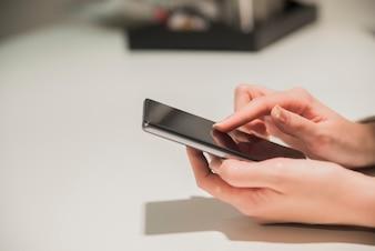 Close-up mãos da menina, sentado na mesa de madeira, em uma mão é smartphone. Mulher de negócios que navega na Internet em smartphone.