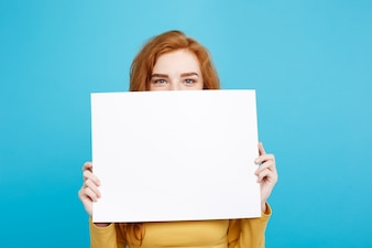 Close up Retrato jovem e bela atraente redhair menina sorridente mostrando sinal em branco. Fundo Pastel Azul. Copie o espaço.