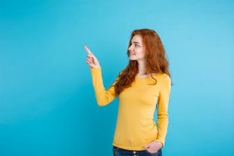 Close up Retrato jovem linda e linda garota redhair feliz com algo e apontar o dedo. Fundo Pastel Azul. Copie o espaço.