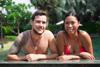 Closeup de casal feliz multi-étnico na borda da piscina