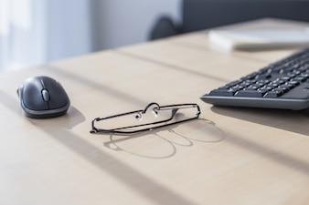 Closeup de laptop, óculos, xícara de café e outros itens no desktop branco com a cidade borrada no fundo