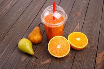 Coctail de desintoxicação de laranja com laranjas e peras está na mesa de madeira