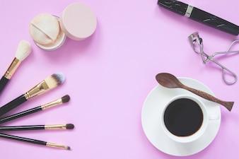 Coleção de maquiagem com uma xícara de café quente, conceito de estilo de vida no fundo rosa