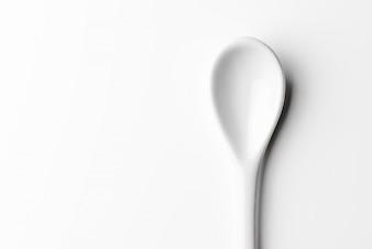Colher branca isolada em uma superfície branca