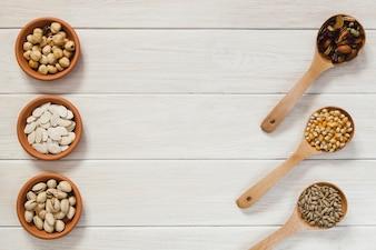 Colheres e tigelas com nozes e sementes
