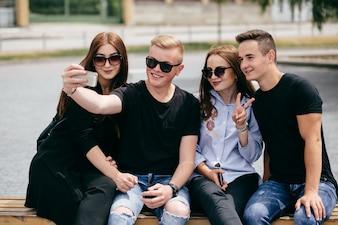Companhia de jovens amigos com smartphones andando na cidade