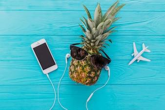 Composição do verão com abacaxi, óculos de sol e telefone móvel