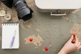 Composição fantástica com corações de colocação de mão no mapa