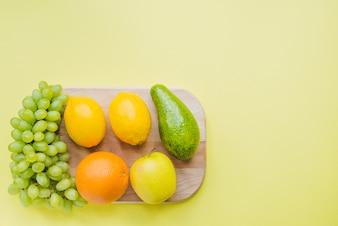 Composição saudável com placa de corte e várias frutas