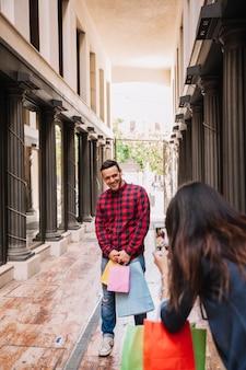 Conceito de compras com menina tirando foto de namorado