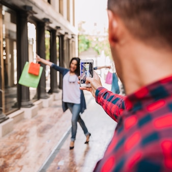 Conceito de compras com menino tirando foto de namorada