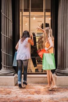 Conceito de compras com mulher olhando a janela da loja