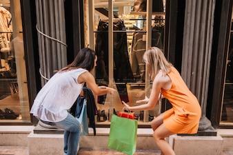 Conceito de compras com mulheres que procuram loja de moda