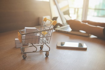 Conceito de compras on-line na internet com laptop e carrinho de compras. Tensão do tom efeito de filtro retro, foco suave (foco seletivo)