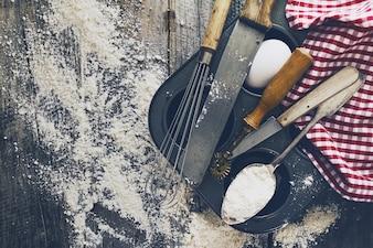Conceito de cozimento cozinha utensílios de cozinha acessórios para assar no fundo de madeira com farinha. Vista do topo. Processo de cozimento. Ninguém.