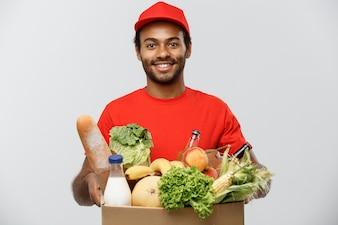 Conceito de entrega - Handsome African American entrega homem carregando pacote de caixa de alimentos e bebidas na loja. Isolado no fundo do estúdio cinzento. Espaço de cópia.