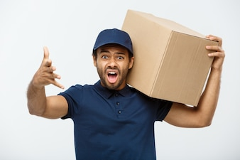 Conceito de entrega - Retrato de homem de entrega serio de afro-americano que mostra expressão agressiva tola, segurando um pacote de caixa. Isolado no fundo do estúdio cinzento. Espaço de cópia.