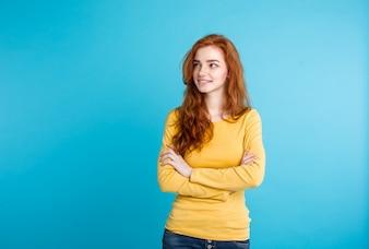Conceito de estilo de vida - Close up Retrato jovem bonito e atraente gengibre menina de cabelo vermelho brincando com o cabelo com timidez. Fundo Pastel Azul. Copie o espaço.
