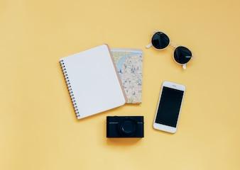 Conceito de itens de viagem: caderno em branco, mapa, câmera, smartphone e óculos de sol em fundo amarelo, vista superior com estilo mínimo