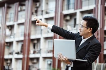 Conceito de negócio - Projeto de plano de homem jovem em sua propriedade com laptop.