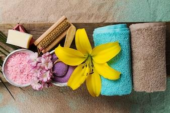 Conceito Dos Termas. Vista superior de produtos bonitos dos termas com lugar para o texto. Óleos essenciais com belas flores, toalhas, sal spa e sabão feito à mão.