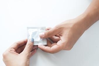 Condom na mão masculina e na mão feminina, dê um conceito de sexo seguro ao preservativo no fundo branco