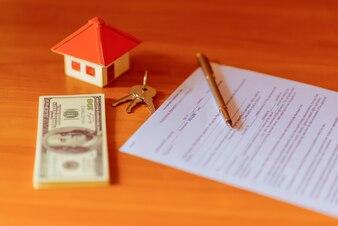 Contrato de venda de corretor imobiliário para acordo de revenda de casa com caneta de tinta e chaves de casa em uma caixa de bloqueio de chaveiro do Realtor (documento fictício com autêntico idioma legal)