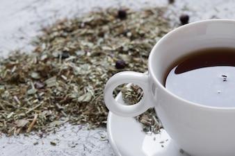 Copo com chá com limão e ervas secas sobre fundo de madeira