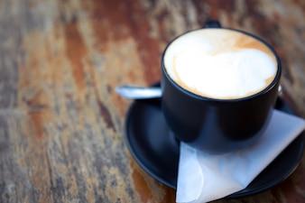 Copo de café escuro em uma mesa de madeira