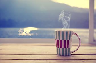 Copo de café quente na mesa de madeira com janela de gota de chuva, horário de verão (tom de cor vintage)
