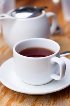 Copo de chá branco e uma panela na mesa de madeira