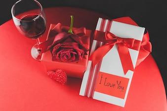 Copo de vinho com presentes e uma rosa em uma tabela vermelha