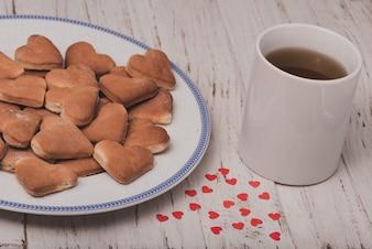 Copo do chá com biscoitos ao lado