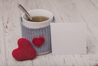Copo do chá com um coração com um papel branco e um coração