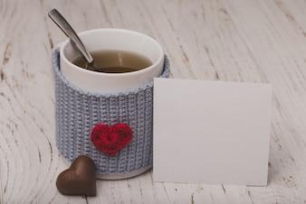 Copo do chá com um coração com um papel branco