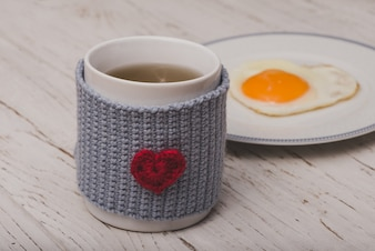 Copo do chá com um ovo frito atrás