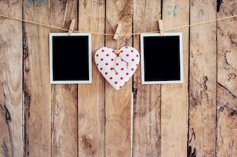 Coração branco e dois moldura fotográfica pendurados na corda da varinha com fundo de madeira.