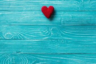 Coração de malha em um fundo de madeira azul