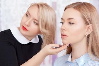 Cosmetologist que olha o espelho do resultado do procedimento.