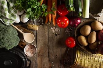 Cozinhando conceito saudável do Detox do vegetal com os vários vegetais, cozinhando o potenciômetro na tabela de cozinha, fundo da cozinha. Vista superior com espaço da cópia.