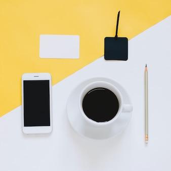 Creative flat lay foto da área de trabalho de mesa com smartphone, café e etiqueta em fundo amarelo e branco, com estilo mínimo