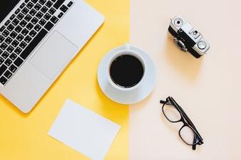 Creative flat lay foto da mesa do espaço de trabalho com laptop, papel em branco, café, óculos e câmera de filme em fundo amarelo moderno