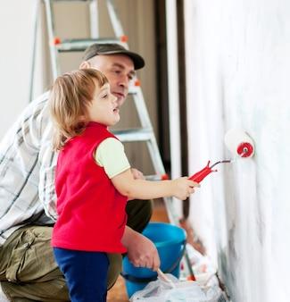 Criança com pai pinta parede