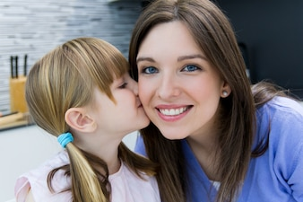 Criança dando um beijo a sua mãe na bochecha